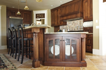 The interior of a rustic country kitchen featuring an elegant stove with built-in wooden cabinetry Stock Photo
