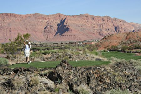 Golfer swings toward fairway with desert red rocks in the background Stock Photo