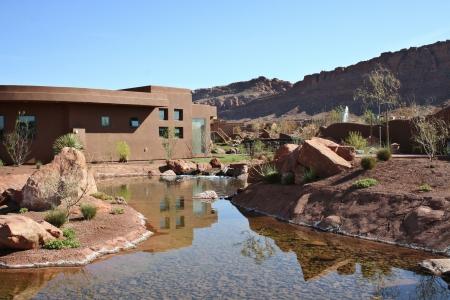 백그라운드에서 폭포와 연못과 붉은 바위 절벽 사막 풍경에 지어진 아름 다운 현대 집 스톡 콘텐츠