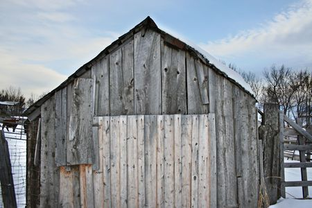 An old barn shed at winter complete with worn and weathered gray wood. Good for vintage, rustic, old or western backgrounds. photo