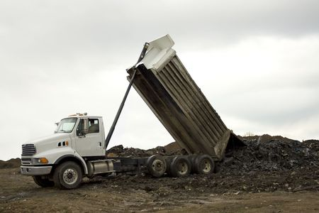 A dump truck unloads its load of waste and dirt on a cloudy day Stock Photo