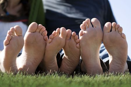 Three sets of clean happy feet all in a row on a sunny day. This is a great photo for a foot doctor (Podiatry or podiatric medicine) website or marketing materials. Stock Photo