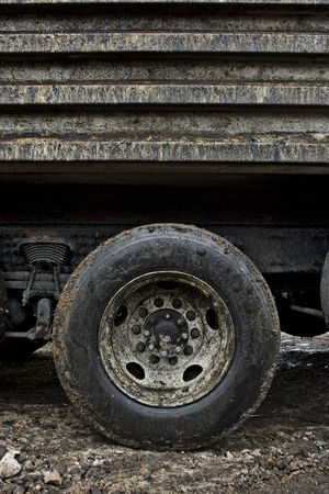 muggy: A close-up of a filthy, muddy, dirty dump truck tire on a wet soggy day. Close details of the muck and mud