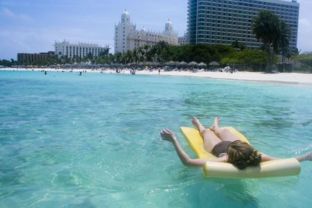 A woman sunbathing. She relaxes while floating in a calm bay along a Caribbean beach with high-rise hotels photo
