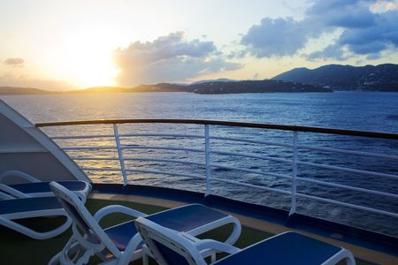 balcony: The sun sets over the caribbean island of St. Thomas as viewed from the balcony of a cruise ship