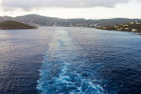 embark: The wake of a large cruise ship as it leaves a port of call out into the Caribbean ocean. The island of St. Thomas can be seen in the background as the ship sails away in the late afternoon. Stock Photo