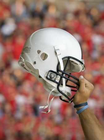 A football player raises his helmet in triumph and celebration during an american football game. (Clipping Path Included) Stock Photo