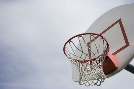 An outdoor basketball basket with the simple backdrop of a cloudy day. Lots of Copy space photo