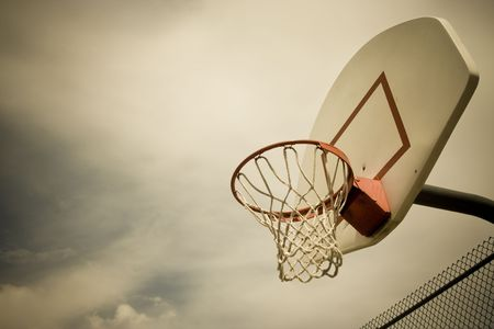processed: A horizontal cross processed basketball hoop background. Lots of Copy space room and cool sepia filter feel. Stock Photo