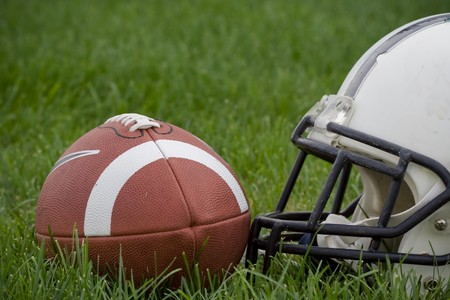 Photo of an American football and a helmet on a grass field (horizontal).