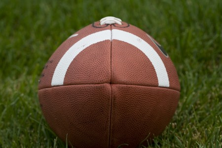 pigskin: A close-up view of an american football on a grassy field
