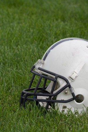 pigskin: The side view of an American football helmet on a grass field. Stock Photo