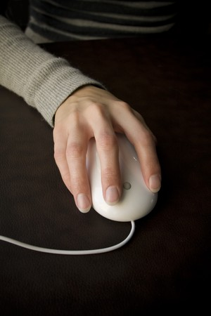 A female hand using a computer mouse to surf the internet photo