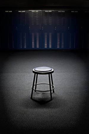A spotlight shines on a lone stool in the middle of a football locker room