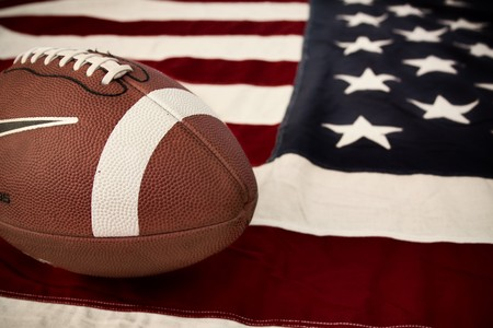 favorite: Football, Americas favorite sport. A ball on a vintage Old Glory. Stock Photo