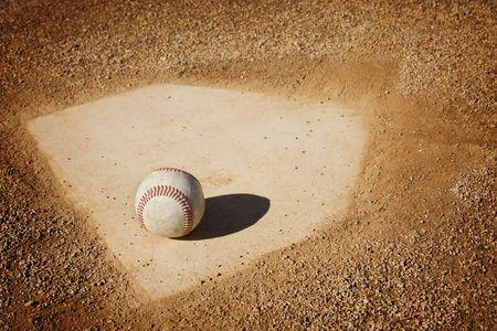 baseball swing: A baseball sitting on home plate. Great sports background
