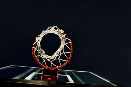 ниже: Basketball basket and net shot from below. A unique view in a basketball arena with only the basket lit. Lots of Copy space room