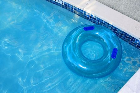 A swimming pool with crystal blue water and a clear inflatable round tube