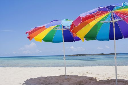 beach umbrella: Colorful Beach umbrellas provide some shade on a beautiful Caribbean beach background