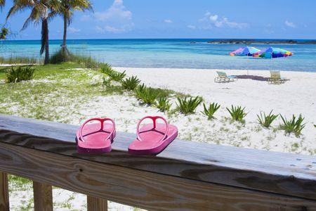 sandalias: Pink Chancletas en la cubierta de un hotel de playa del Caribe. Sombrillas, palmeras, arena blanca y aguas azul aqua-en el fondo