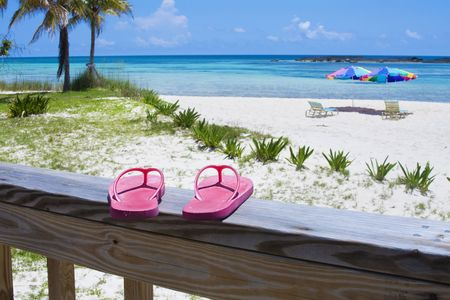 Pink Flip flops on the deck of a Caribbean beach resort. Beach umbrellas, palm trees, white sand and aqua-blue waters in the background Stock Photo