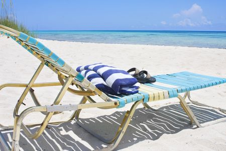 An inviting lounge chair with towel and flip flops sitting on a beautiful Caribbean beach Stock Photo - 5194503