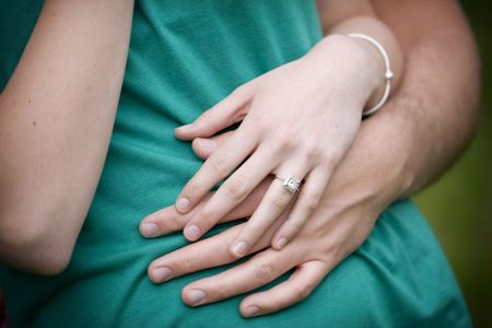 A young woman displays her engagement ring while her fiancee holds her tightly. Selective focus on the hands Stock Photo