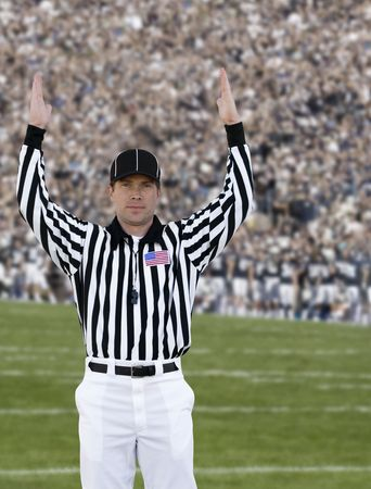 referees: A football official signals touchdown at a football game