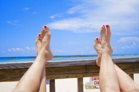 feet relaxing: Two women prop their feet up on a deck at an oceanside vacation resort, Just Relaxing!