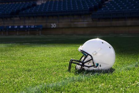 football grass: Football Helmet at the Stadium Stock Photo