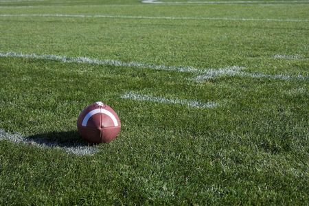 A football rests on the playing field in a stadium. Lots of copy space