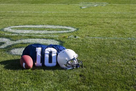 A football helmet, should pads and ball rest on the playing field in a stadium. photo