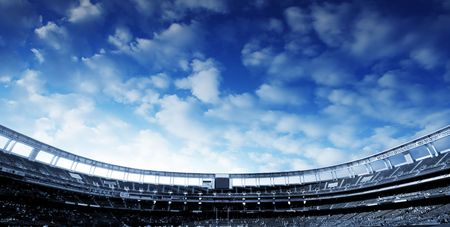 Wide Horizontal photo of a american football stadium with blue clouds in the sky Stock Photo