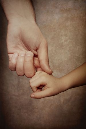 A father reaches down and holds the hand of his child photo