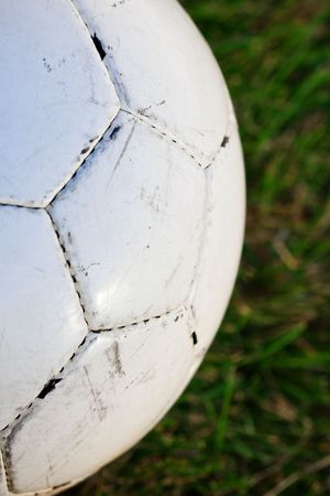 close up photo of a white soccer ball on a grassy field photo