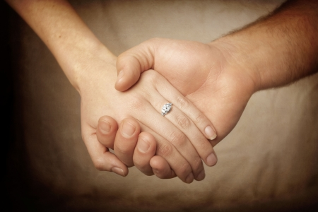 close-up view of a newly engaged couple holding hands. The symbol of commitment and marriage photo