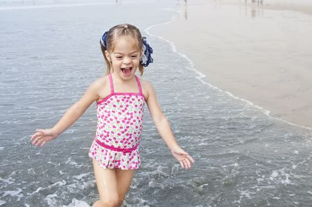 A cute little girl playing on the beach enjoying the summertime Stock Photo