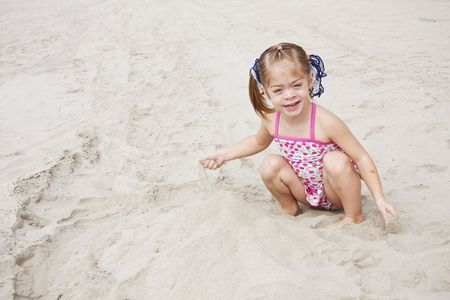 A cute little girl playing in the sand on the beach enjoying her summer vacation. Lots of copy space photo