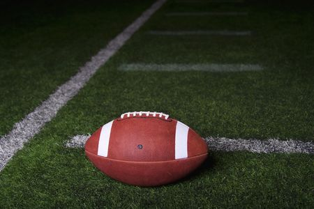 Football resting on a turf field at night. Lots of copy space with dramatic lighting