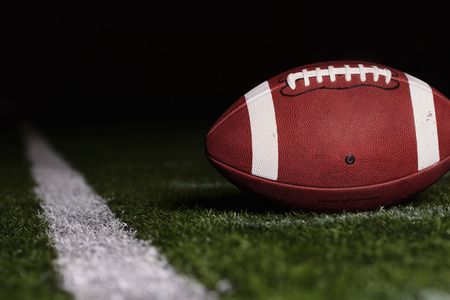 american football background: Football resting on the first down line