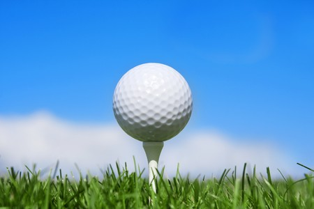 blue green background: Golf Ball on a tee horizontal