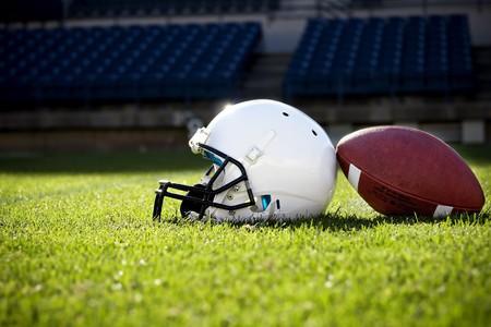 athletic gear: Football Helmet on a stadium field Stock Photo