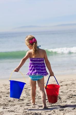 Cute little girl busy building sand castles on the beach photo