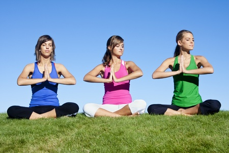 A group of beautiful young women doing yoga together photo