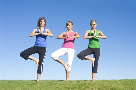 three attractive women exercising and doing yoga together photo