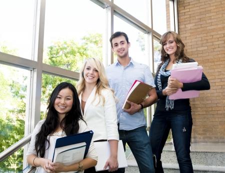 Grupo de jóvenes alumnos y alumnas dentro de un edificio académico Foto de archivo - 9775113