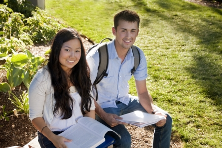 Young, attractive male and female students outside studying Stock Photo - 9775133