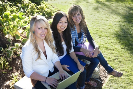 A group of Young, attractive female students outside studying Imagens