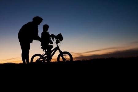 Parent aider un enfant à apprendre à monter un vélo Banque d'images