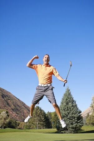 winnings: A young golfer jumping in the air in excitement about making a put Stock Photo